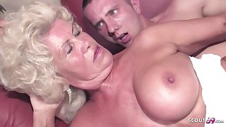 Blonde granny with a super queasy pussy and big, fake tits is going to bed a younger guy